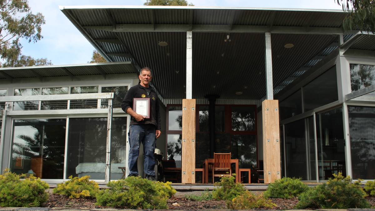 Mr Briggs out the back of the stunning Millingandi home holding his MBA Excellence in Regional Building Award.